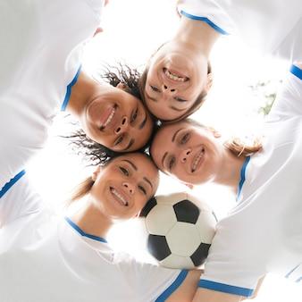 Widok z dołu kobiety trzymającej piłkę z bliska