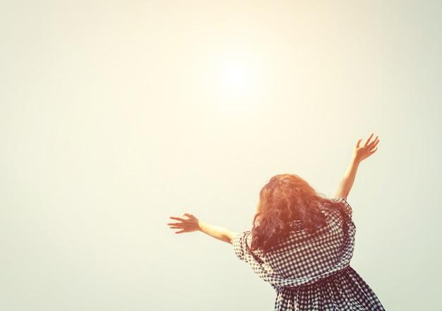 Widok z dołu kobiety z otwartymi ramionami, patrząc na niebo