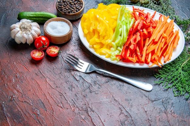 Widok z dołu kolorowe krojone papryki na talerzu widelec sól i czarny pieprz pomidory czosnek ogórek na ciemnoczerwonym stole