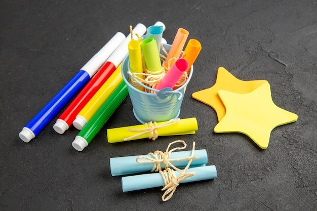 Widok z dołu kolorowe markery zwinięte karteczki samoprzylepne przewiązane liną w małym wiaderku karteczki samoprzylepne gwiazdki na czarnym stole