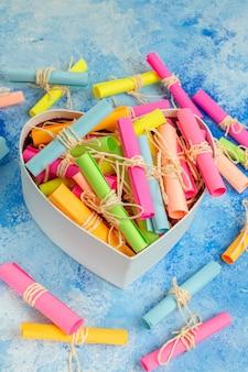 Widok z dołu koncepcja walentynki przewiń papiery życzeń w pudełku w kształcie serca na niebieskim tle