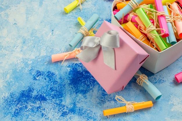 Widok z dołu koncepcja walentynki przewiń życzeń papiery w pudełku w kształcie serca prezenty na niebieskim tle miejsce kopiowania