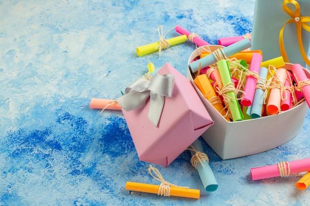 Widok z dołu koncepcja walentynki przewiń życzeń papiery w pudełku w kształcie serca prezenty na niebieskim tle z wolną przestrzenią