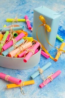 Widok z dołu koncepcja walentynki przewiń życzenia papiery w pudełku w kształcie serca prezent na niebieskim tle zdjęcie stockowe