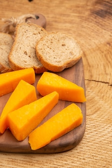 Widok z dołu kromki sera kromki chleba na desce do krojenia na stole