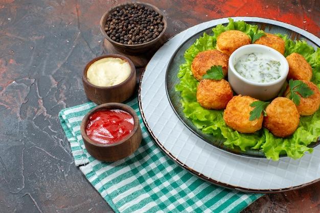 Widok z dołu kurczaka sałata i sos na talerzu czarny pieprz w misce sosy w małych miseczkach na ciemnym stole