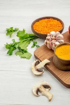 Widok z dołu lentile miska czosnek kurkuma na desce do krojenia grzyby pietruszka na szarym stole
