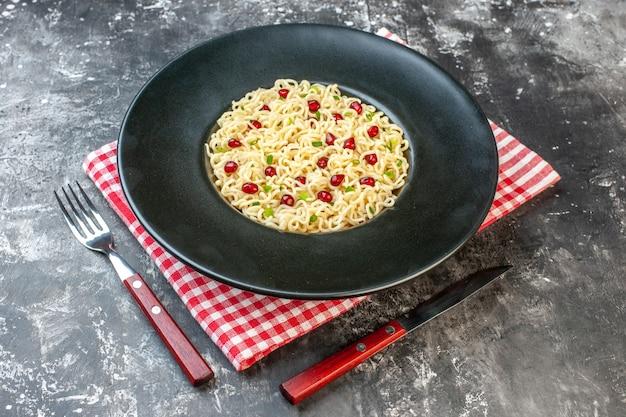 Widok z dołu makaron ramen na ciemnym okrągłym talerzu czerwona biała serwetka w kratkę widelec i nóż na ciemnym stole