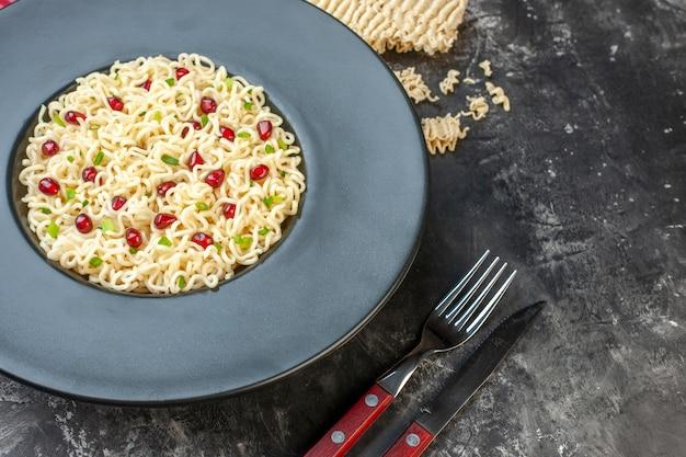 Widok z dołu makaron ramen na ciemnym okrągłym talerzu obrus w czerwoną i białą kratkę widelec i nóż surowy makaron ramen na ciemnym stole