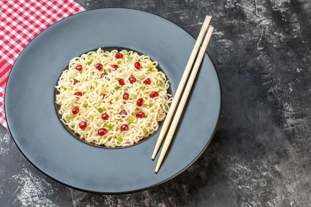 Widok z dołu makaron ramen z pałeczkami z granatów na ciemnym okrągłym talerzu czerwona biała serwetka w kratkę na ciemnym stole