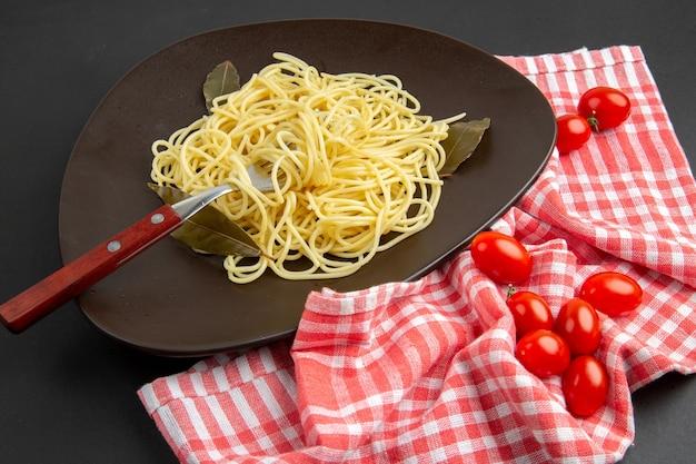 Widok z dołu makaron spaghetti z liśćmi laurowymi widelec na talerzu pomidorki koktajlowe czerwony i biały ręcznik kuchenny w kratkę na czarnym stole