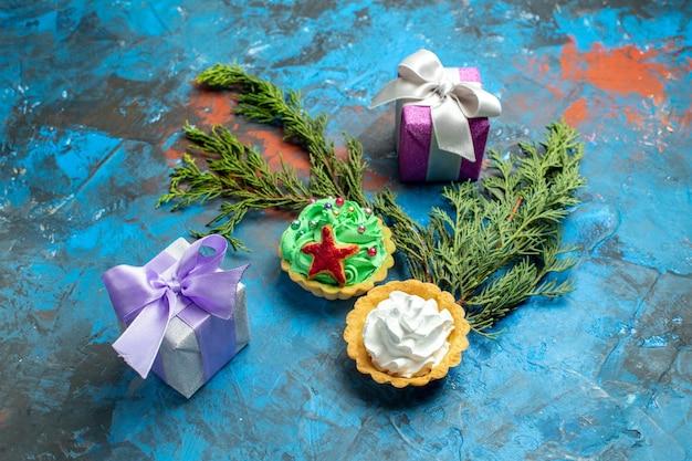 Widok z dołu małe tarty małe prezenty gałęzie sosny na niebiesko-czerwonej powierzchni