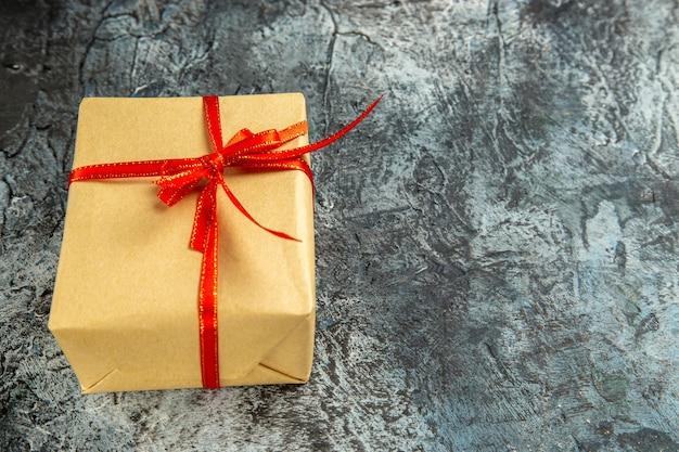 Widok z dołu mini prezent związany z czerwoną wstążką na ciemnym na białym tle przestrzeni kopii