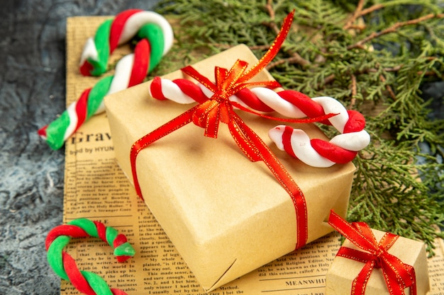 Widok z dołu mini prezent związany z czerwoną wstążką świątecznych cukierków na gazecie na szarym tle