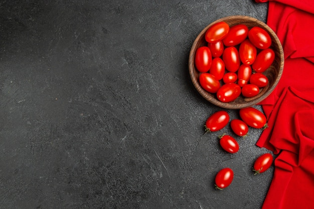 Widok z dołu miska z czerwonym ręcznikiem pomidorkami cherry i pomidorkami na ciemnym tle