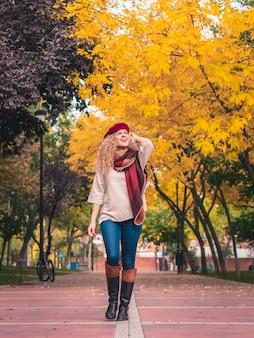Widok z dołu młodej kobiety z czerwoną francuską czapką, szalikiem i butami, uśmiecha się, patrząc na piękne kolory jesieni podczas spaceru