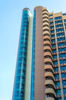 Widok z dołu na nowoczesny budynek. wieżowiec naprzeciw błękitnego nieba w słoneczny dzień