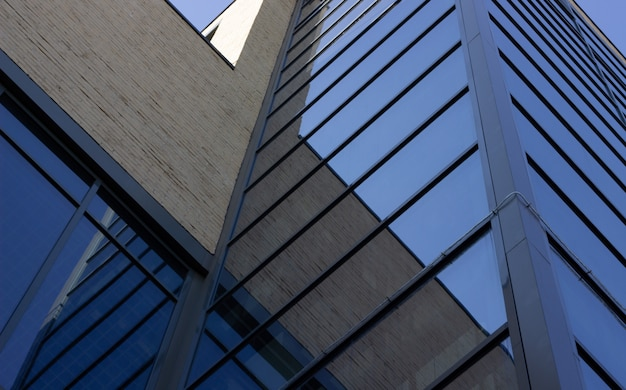 Widok z dołu na nowoczesny budynek ze szklanymi oknami