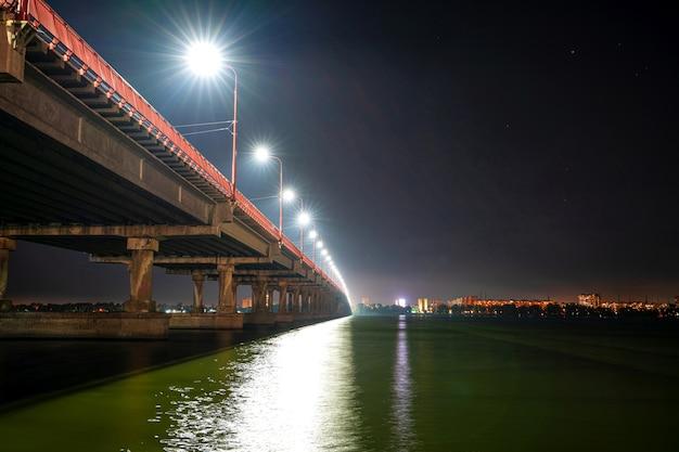 Widok z dołu na piękny jasny długi most nad dużą piękną rzeką dniepr