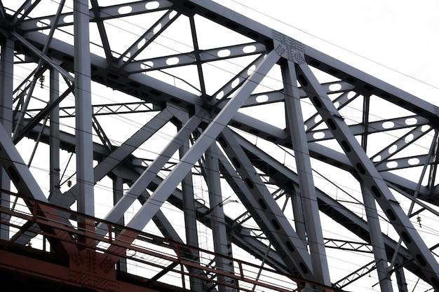 Widok z dołu na sekcję kolejowego mostu kratownicowego na tle zachmurzonego nieba