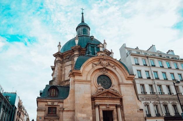 Widok z dołu na temple du marais i pochmurne niebo w paryżu, francja