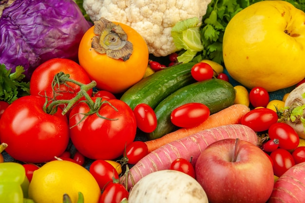 Widok z dołu owoce i warzywa rzodkiewka pomidorki koktajlowe pomidory persymona ogórek kiwi jabłka czerwona kapusta pietruszka pigwa na niebieskim stole