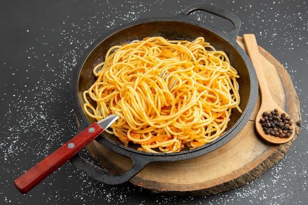 Widok z dołu patelnia do spaghetti czarny pieprz w drewnianej łyżce na desce na ciemnym tle