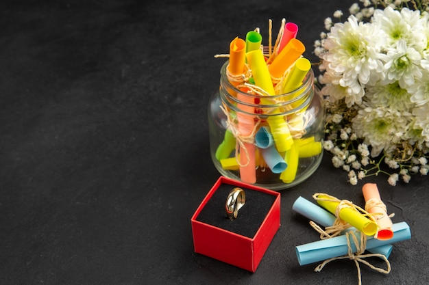 Widok z dołu pierścionek zaręczynowy w pudełku bukiet kwiatów przewijanie życzeń w słoiku na ciemnym tle z wolnym miejscem
