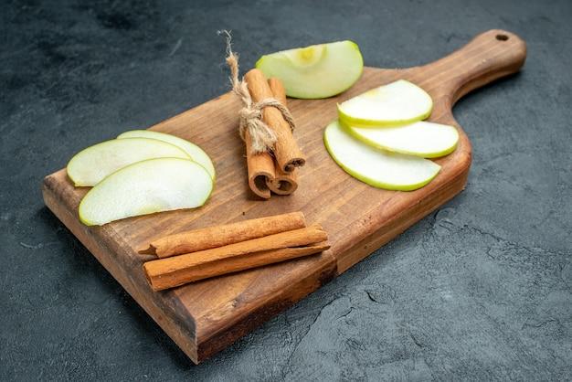 Widok z dołu plasterki jabłka i laski cynamonu na desce do krojenia na ciemnym stole