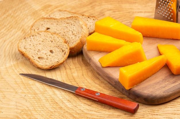 Widok z dołu plasterki tarki do serów na desce do krojenia kromki chleba na ziemi