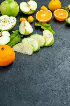 Widok z dołu pokrojone jabłka i liście mandarynki cumcuat na ciemnym miejscu na stole