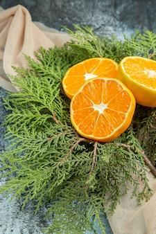 Widok z dołu pokrojone pomarańcze na gałęzie sosny na ciemnej powierzchni