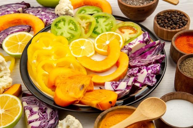 Widok z dołu pokrojone warzywa i owoce dynia papryka persimmon czerwona kapusta zielone pomidory na czarnym talerzu przyprawy w miseczkach na drewnianym stole
