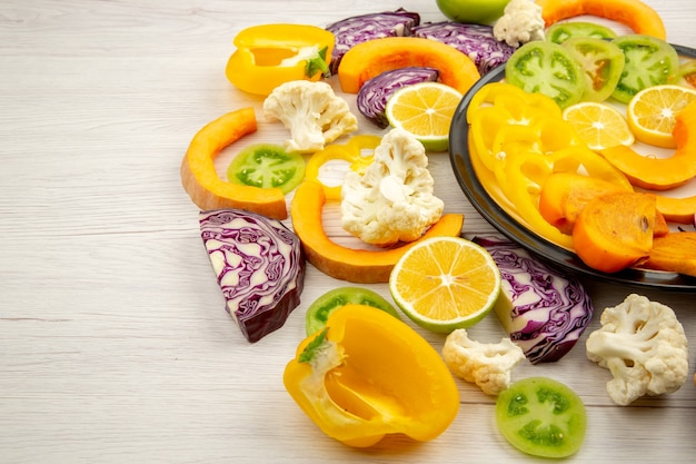 Widok z dołu pokrojone warzywa i owoce papryka dynia persimmon czerwona kapusta zielone pomidory na czarnym talerzu na drewnianym stole