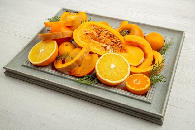 Widok z dołu pół dyni piżmowej pokrojone w pomarańczowe mandarynki persimmons na ramie na białym stole