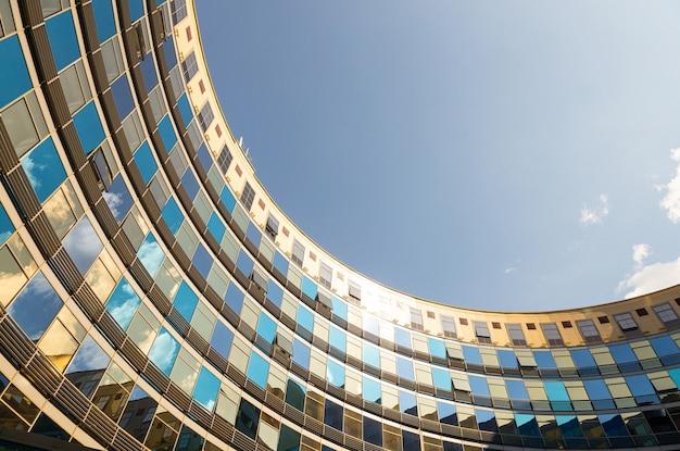 Widok z dołu półkola budowanego ze szklanymi ścianami w kolorach niebieskim i złotym