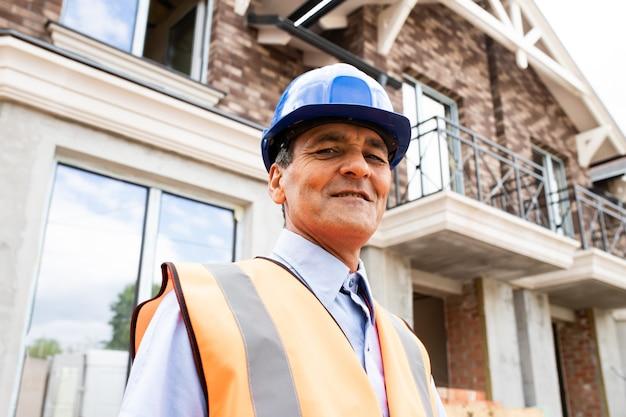Widok z dołu portret radosnego indian american man architekta na placu budowy patrząc na kamery pracownik budowlany ubrany w niebieski kask i zachód uśmiecha się do kamery