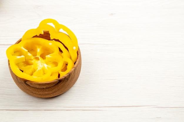 Widok z dołu posiekanej żółtej papryki w drewnianej misce na białym stole wolnej przestrzeni