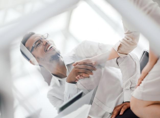 Widok z dołu pracowników uścisk dłoni przy biurku w biurze. zdjęcie z miejscem na kopię