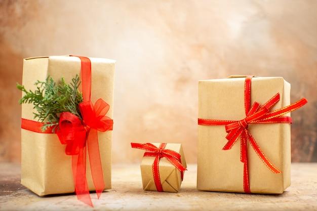 Widok z dołu prezenty świąteczne w brązowej papierowej wstążce choinkowe zabawki na gazecie na beżowym tle