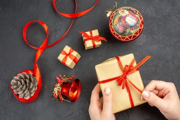 Widok z dołu prezenty świąteczne w brązowej papierowej wstążce zabawki choinkowe na gazecie na beżu