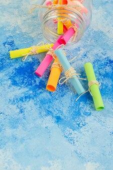 Widok z dołu przewiń kolorowe papiery życzeń rozrzucone ze słoika na niebieskim tle wolnej przestrzeni
