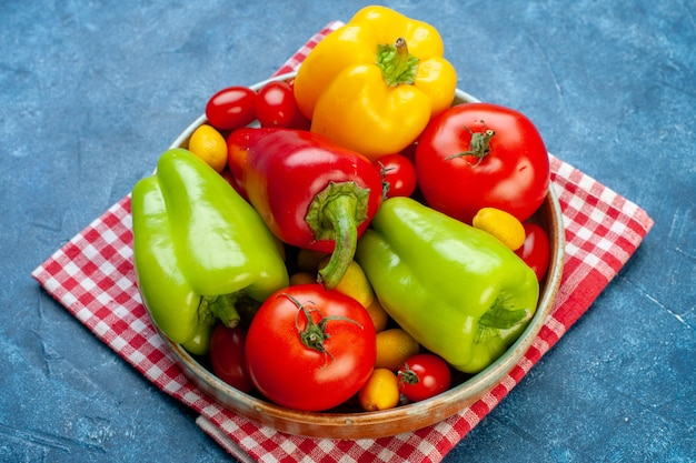 Widok z dołu różne warzywa pomidory koktajlowe różne kolory papryka pomidory cumcuat na talerzu na czerwono biały ręcznik kuchenny w kratkę na niebieskim stole