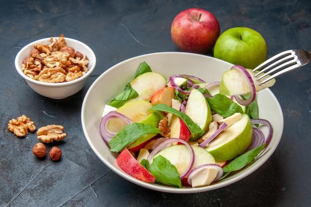 Widok z dołu sałatka jabłkowa w misce plasterek jabłka na widelcu orzech w misce czerwone i zielone jabłka na ciemnym izolowanym stole