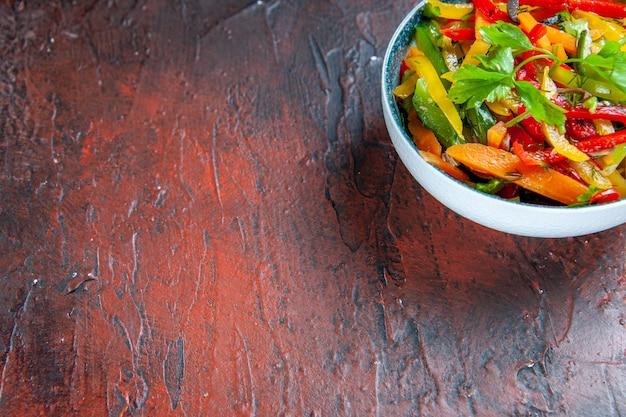 Widok z dołu sałatka jarzynowa w misce na ciemnoczerwonym stole wolnym miejscu