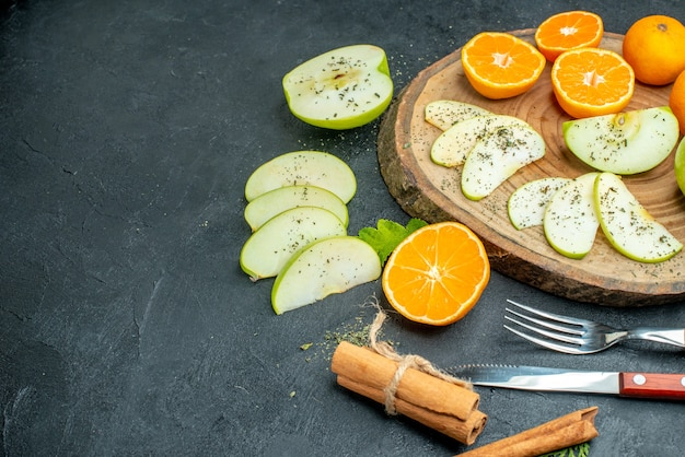 Widok z dołu siekanie jabłek i mandarynek z suszonym proszkiem miętowym na desce cynamonowej widelec i nóż na ciemnym wolnym miejscu na stole