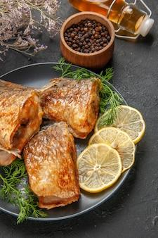 Widok z dołu smażona ryba z plasterkami cytryny na talerzu czarnym pieprzem w drewnianej misce butelka oleju na ciemnym tle