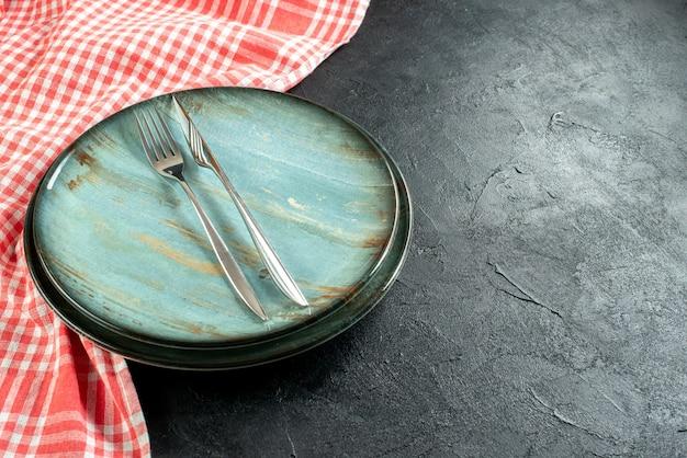 Widok z dołu stalowy widelec i nóż obiadowy na okrągłym talerzu czerwony i biały obrus w kratkę na czarnym stole