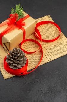 Widok z dołu świąteczny prezent w brązowej wstążce jodły gałęzi papieru na gazecie na ciemnym tle