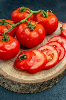Widok z dołu świeże czerwone pomidory posiekane pomidory na rustykalnej okrągłej desce na czarnym stole